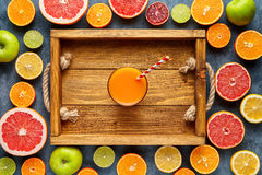 Smoothie or fresh juice in wooden tray in citrus fruits background flat lay, healthy lifestyle vegan organic antioxidant royalty free stock image