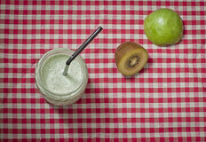 Smoothie fruits with yogurt. Smoothie yogurt, kiwifruit and apples in glass jar on gingham table cloth Royalty Free Stock Image