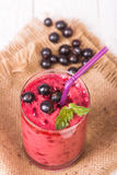 Smoothie in a glass and fresh currants. Currant smoothie in a glass on a wooden table Royalty Free Stock Photography