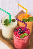 Smoothie in a glass and fresh fruits and berries. Fresh berries and fruit, and smoothies in a glass on the table Stock Photos