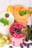 Smoothie in a glass and fresh fruits and berries. Fresh berries and fruit, and smoothies in a glass on the table Royalty Free Stock Photos