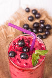 Smoothie in a glass and fresh fruits and berries. Fresh berries and fruit, and smoothies in a glass on the table Stock Images