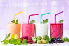 Smoothie in a glass and fresh fruits and berries. Smoothies in glasses of different fruits on a wooden table Royalty Free Stock Images