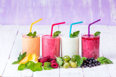 Smoothie in a glass and fresh fruits and berries. Smoothies in glasses of different fruits on a wooden table Stock Photo