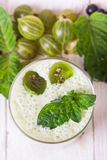 Smoothie in a glass and fresh gooseberries. Gooseberries smoothie in a glass on a wooden table Stock Photos