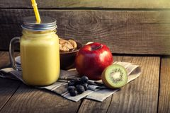 Smoothie in glass jar on rustik wood. Green healthy beverage and royalty free stock photo
