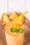 Smoothie in a glass and slices of fresh peaches. On a wooden table Royalty Free Stock Photo
