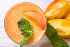 Smoothie in a glass and slices of fresh peaches. Peaches smoothie in a glass on a wooden table Stock Images