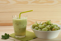 Smoothie from gooseberries in a glass and gooseberries in bowl Stock Image