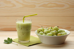 Smoothie from gooseberries in a glass and gooseberries in bowl