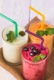 Smoothie i ett exponeringsglas och nya frukter och bär Arkivfoton
