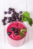 Smoothie i ett exponeringsglas och nya frukter och bär Arkivbild