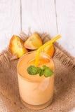 Smoothie i ett exponeringsglas och skivor av nya persikor Fotografering för Bildbyråer