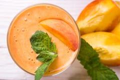 Smoothie i ett exponeringsglas och skivor av nya persikor Arkivbilder