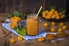 Smoothie jaune de prune dans le verre, la confiture et la prune jaune mûre sur la table en bois Bio nourriture et boisson saines Photos stock