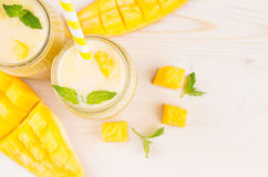 Smoothie jaune fraîchement mélangé de fruit de mangue dans des pots en verre avec la paille, feuilles en bon état, tranches de ma Images libres de droits