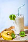 Smoothie with kiwi and banana. A glass of green kiwi and banana smoothie with fresh kiwis and fresh banana stock images