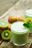 Smoothie kiwi in a glass. On a dark wood background. tinting. selective focus stock photos