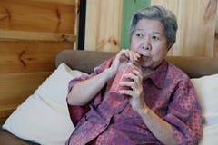 Smoothie mélangé potable de baies de dame supérieure plus âgée à la maison Asiatique Photographie stock libre de droits