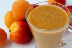Smoothie made with peach and apricot. On a white background Royalty Free Stock Photos