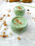 Smoothie made of pears and spinach. With granola for healthy nutrition stock photo