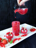 Smoothie made of red berries is being poured with glass jug into different glass vessels Royalty Free Stock Image