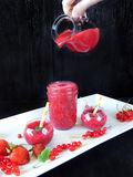 Smoothie made of red berries is being poured with glass jug into different glass vessels. Smoothie made of red berries for healthy nutrition is being overpoured Royalty Free Stock Images