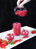 Smoothie made of red berries is being poured with glass jug into different glass vessels Royalty Free Stock Images