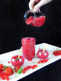 Smoothie made of red berries is being poured with glass jug into different glass vessels Royalty Free Stock Photography