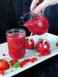 Smoothie made of red berries is being poured with glass jug. Into different glass vessels Royalty Free Stock Images