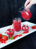 Smoothie made of red berries is being poured with glass jug. Into different glass vessels Stock Photography