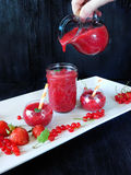 Smoothie made of red berries is being poured with glass jug. Into different glass vessels Stock Images