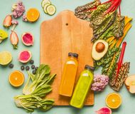 Smoothie making concept. Various healthy fresh fruits and vegetables with bottles on light mint table background with cutting boar. D, top view , frame. Detox Royalty Free Stock Photo