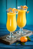 Smoothie mango-banana-orange. A smoothie with mango, banana and orange decorated with mandarins stock images