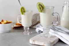 Smoothie mezclado fresco de la proteína del kiwi con el yogur o la leche en el tarro de cristal, consumición sana fotos de archivo libres de regalías