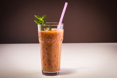 Smoothie with mint and straw. Glass of smoothie made of blackberries, oranges, yogurt and strawberries Royalty Free Stock Photo