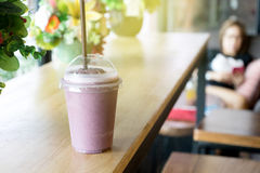 Smoothie mix berry. In plastic cup on wood table bar with blur woman background Royalty Free Stock Images