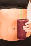 Smoothie modifié la tonalité de fruit mélangé par corps bronzé par torse femelle mince photo stock
