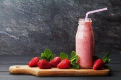 Smoothie o batido de leche de la fresa en tarro en el fondo rústico negro, comida sana para el desayuno Fotografía de archivo