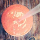 Smoothie. Pink juice mango strawberry drink glass straw wooden table Stock Image
