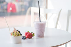 Smoothie in plastic cup and frozen yougurt with fruits. At the white table stock photos