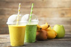 Smoothie in plastic cup. Green and yellow smoothie in plastic cup with fruits on wooden table stock photo