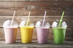 Smoothie in plastic cups. Sweet smoothie in plastic cups on grey wooden table stock photo