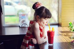 Smoothie potable de fraise de fille d'enfant images stock