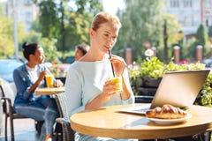 Smoothie potable de jeune femme et vidéo de observation sur l'ordinateur portable Image stock