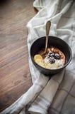 Smoothie puchar z lody, czernicami, bananów plasterkami i chia ziarnami na waniliowym i czekoladowym drewnianym checke i tle zdjęcie stock