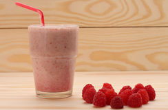 Smoothie from raspberries  in a glass and raspberries  on wooden Royalty Free Stock Photo