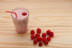 Smoothie from raspberries in a glass and raspberries on wooden