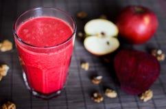 Smoothie rojo del otoño crudo fresco del vegano hecho de las remolachas, de zanahoria, de manzana y de las nueces en el fondo osc Fotos de archivo