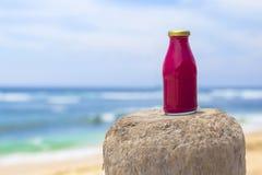 Smoothie rojo sano con la playa imagen de archivo